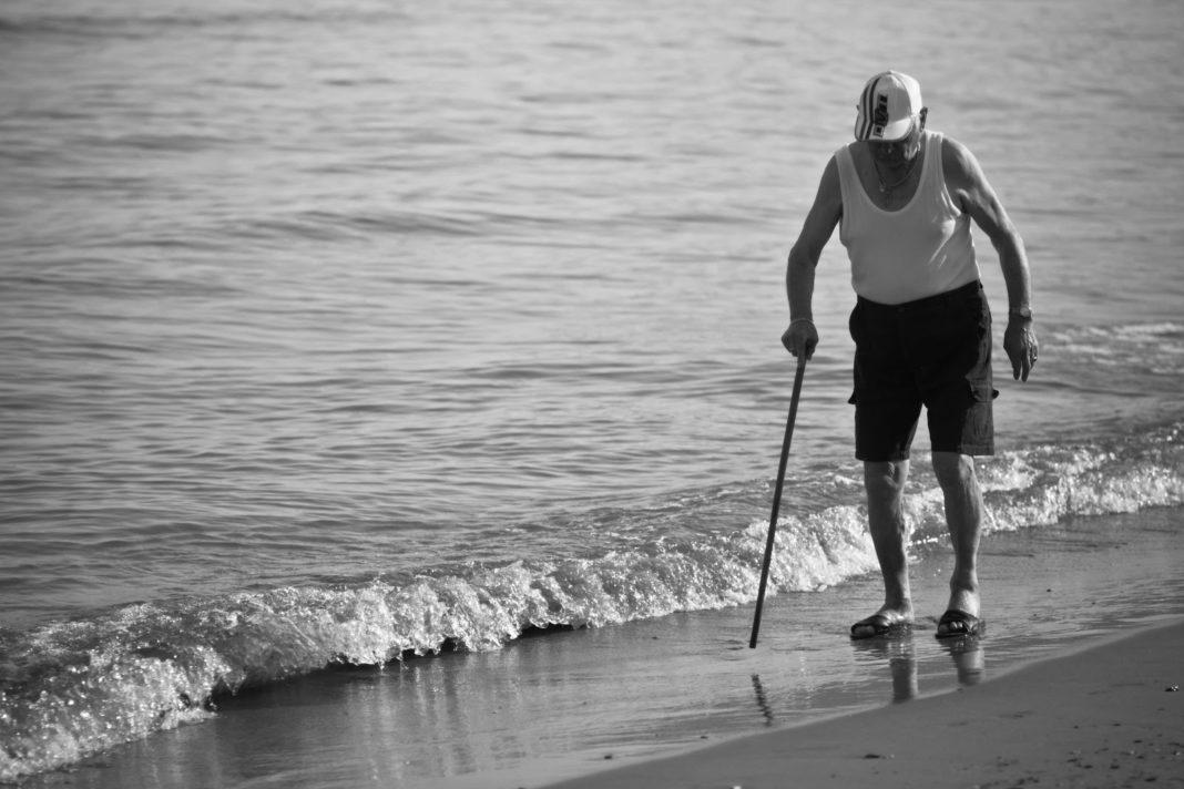 anziano sulla riva di una spiaggia