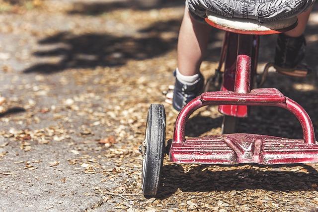 bambino guida un triciclo