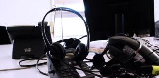 cuffie e telefoni su una scrivania di un help desk